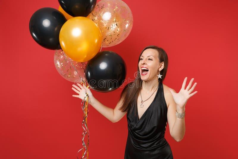 Radosna młoda dziewczyna w małej czerni sukni odświętności, podesłanie ręki, mienie lotniczy balony odizolowywający na czerwonym  fotografia royalty free