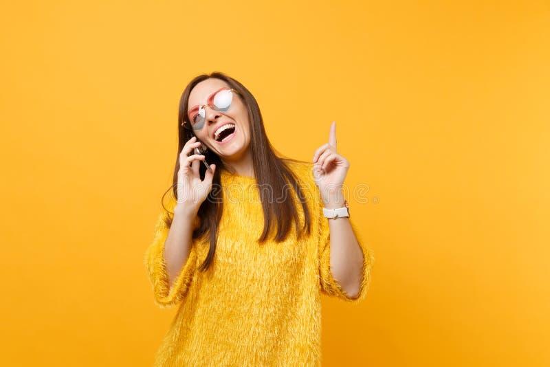 Radosna młoda kobieta wskazuje palec wskazującego w górę opowiadać na telefonie komórkowym prowadzi przyjemną rozmowę w kierowych zdjęcie royalty free