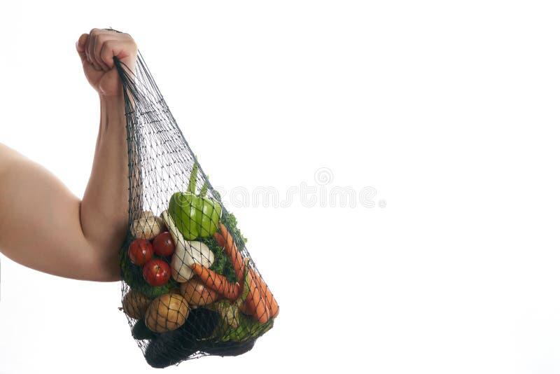 Radosna mężczyzna atleta trzyma torba na zakupy warzywa pełno zdjęcie royalty free