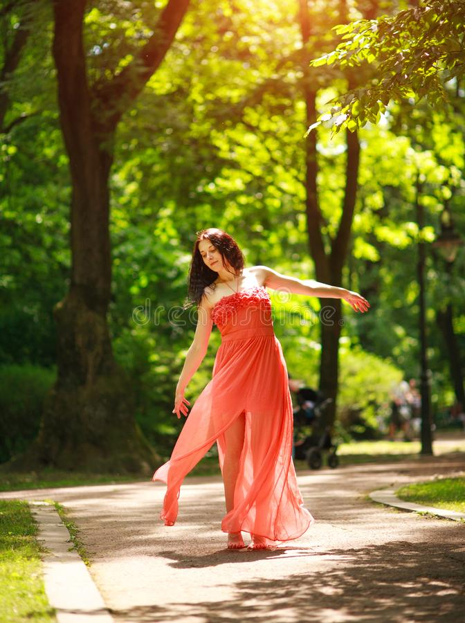 Radosna młoda kobieta cieszy się tana w zielonym miasto parku na naturze wśród drzew, pojęciu wolność i niedbalstwie, zdjęcia stock