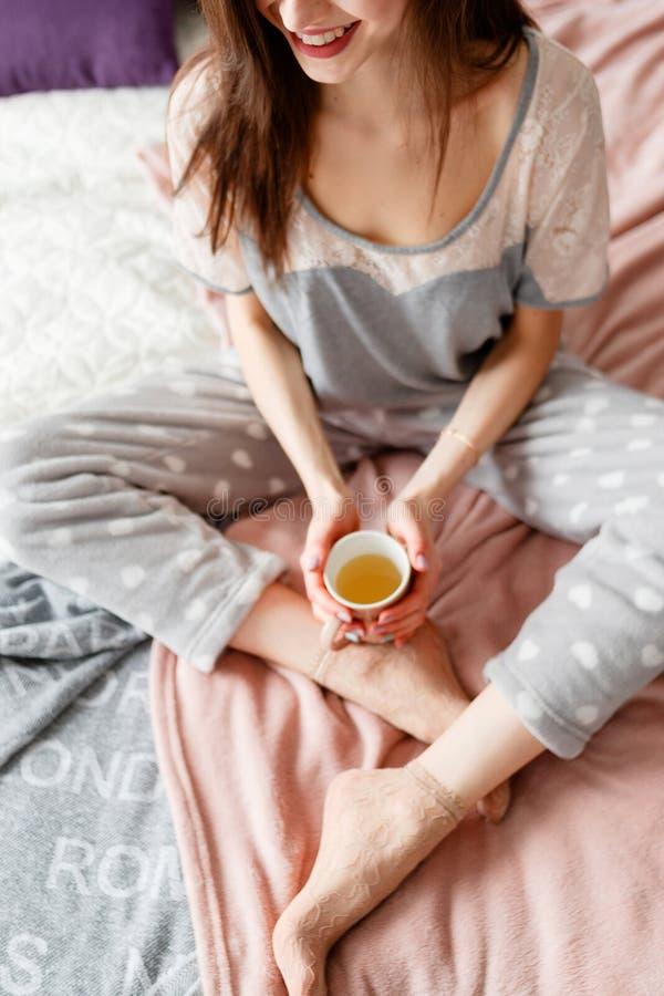Radosna młoda kobieta tenderly trzyma filiżankę herbata zdjęcie stock