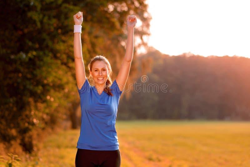 Radosna młoda kobieta uderza pięścią powietrze obrazy stock