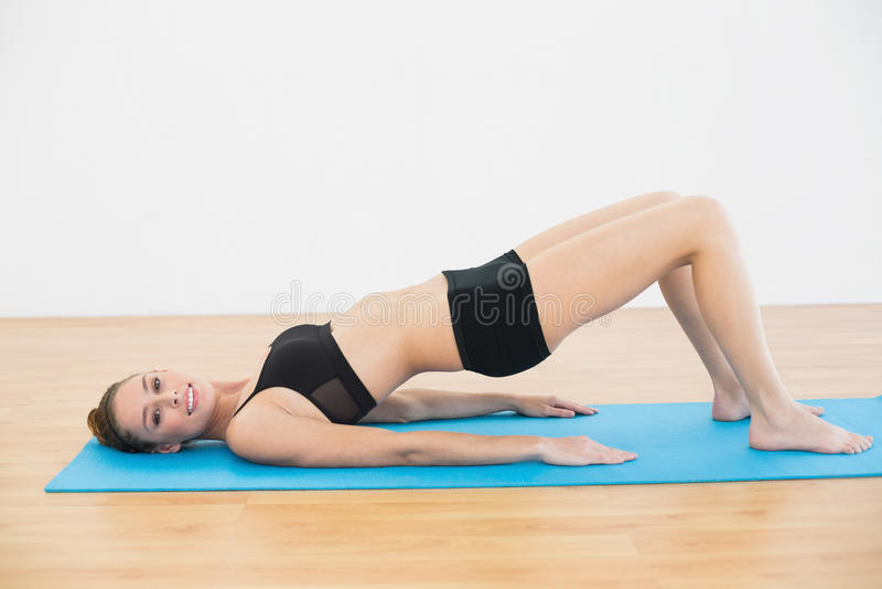 Radosna młoda kobieta w sportswear lying on the beach na ćwiczenia matowy robić ćwiczy fotografia royalty free