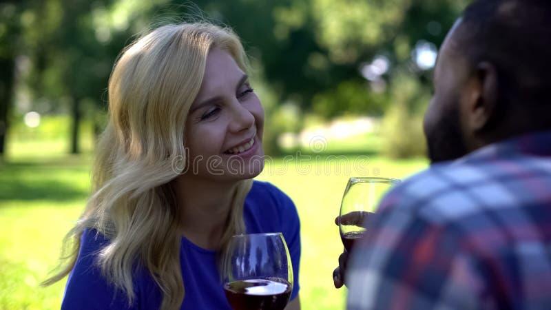 Radosna para wznosi toast wino w i pije parku, romantycznej dacie i pinkinie, zdjęcia royalty free