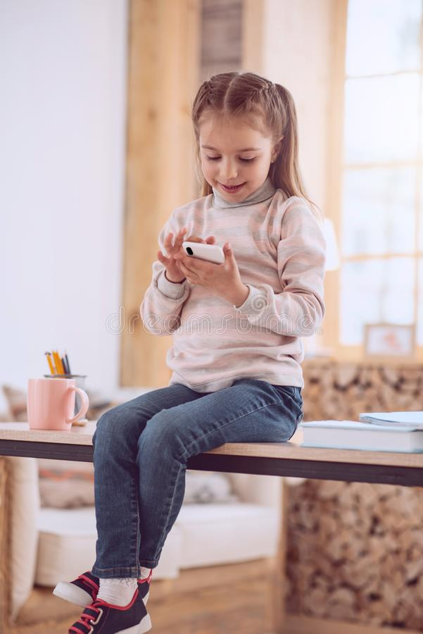 Radosna pozytywna dziewczyna trzyma jej smartphone zdjęcia royalty free