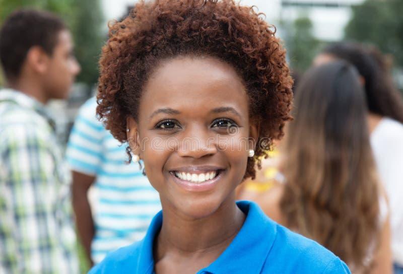 Radosna roześmiana amerykanin afrykańskiego pochodzenia kobieta z grupą przyjaciele zdjęcia stock