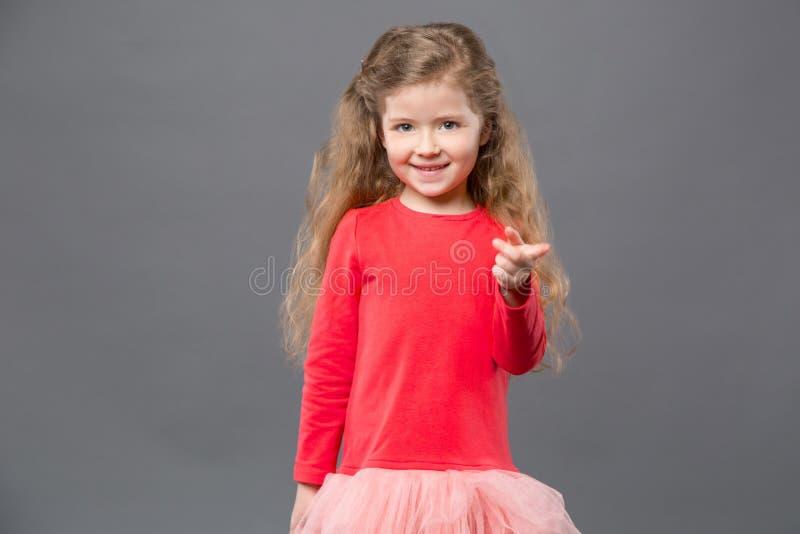 Radosna słodka dziewczyna wskazuje przy tobą zdjęcia stock