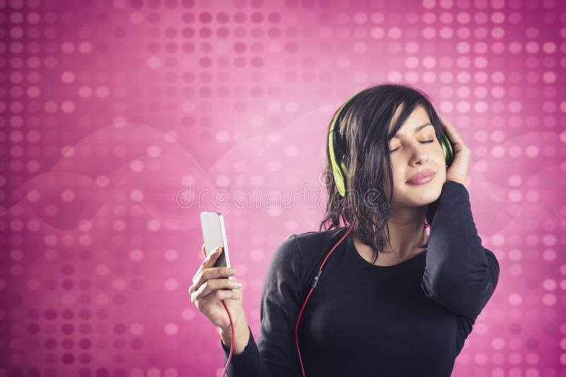 Radosna spokojna dziewczyna cieszy się słuchać muzyka z hełmofonami zdjęcie stock