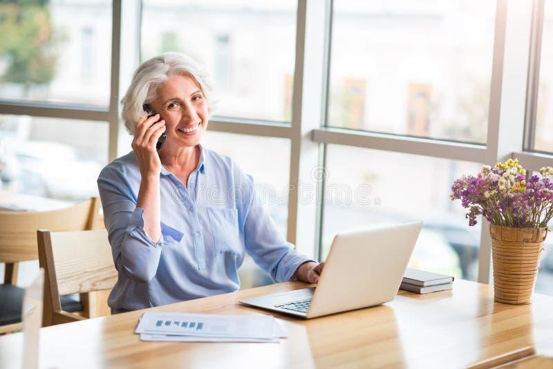 Radosna starsza kobieta opowiada na telefonie komórkowym obrazy stock