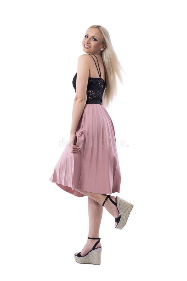 Radosna szczęśliwa młoda kobieta pozuje w łosoś plisującym spódnicy i koronki wierzchołku z nastroszoną nogą obrazy stock