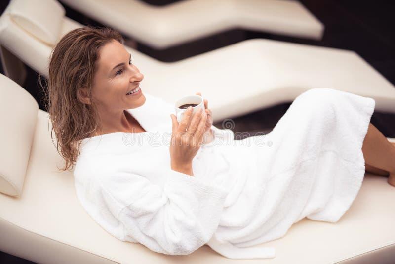 Radosna w średnim wieku dama trzyma filiżankę gorący napój w białym bathrobe obraz stock
