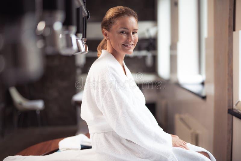 Radosna w średnim wieku kobieta odpoczywa przy wellness centrum zdjęcia royalty free