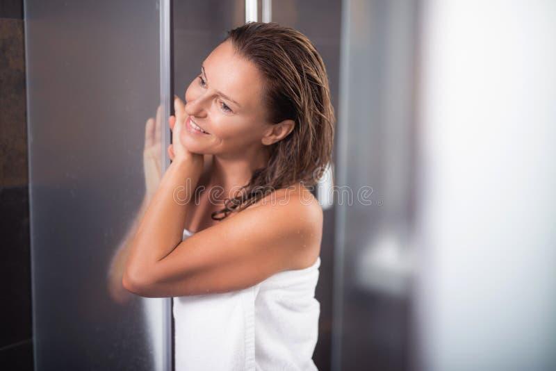 Radosna w średnim wieku kobieta opiera przeciw prysznic drzwi fotografia royalty free