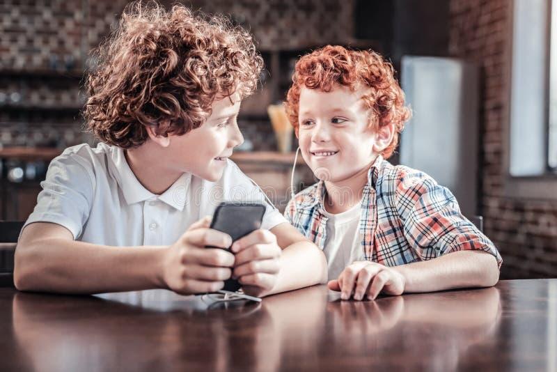 Radosne ładne chłopiec słucha muzyka fotografia stock