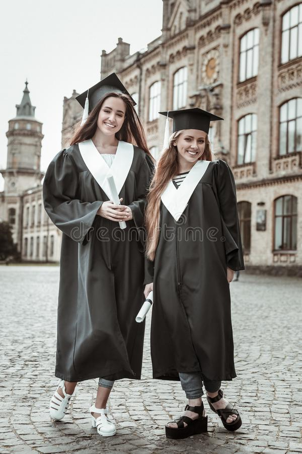 Radosne dziewczyny ma skalowania przyjęcia przy uniwersytetem obrazy stock