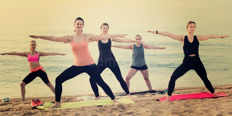 Radosne sporty kobiety ćwiczy joga pozycje obraz stock