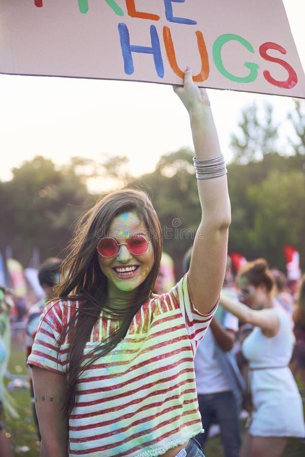 Radosnego kobiety mienia sztandaru «bezpłatni uściśnięcia podczas lato festiwalu muzykiego obrazy stock