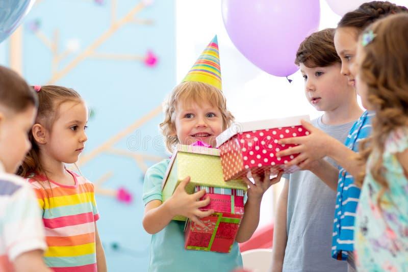 Radosnej ma?e dziecko ch?opiec odbiorczy prezenty przy przyj?ciem urodzinowym Wakacje, urodzinowy poj?cie obrazy royalty free