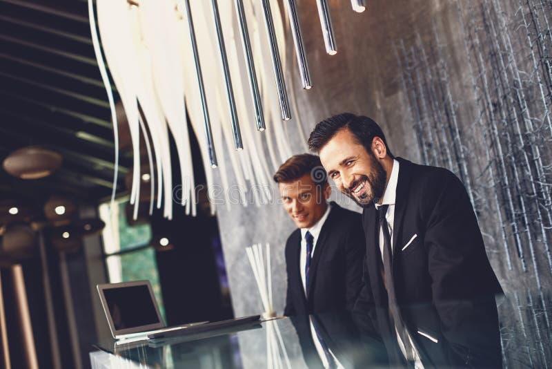Radosni hotelowcy siedzÄ…cy przy recepcji i uÅ›miechajÄ…cy siÄ™ patrzÄ…c na ciebie zdjęcia royalty free