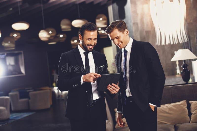 Radosni przyjaciele uÅ›miechajÄ… siÄ™ patrzÄ…c na nowoczesny tablet obraz royalty free