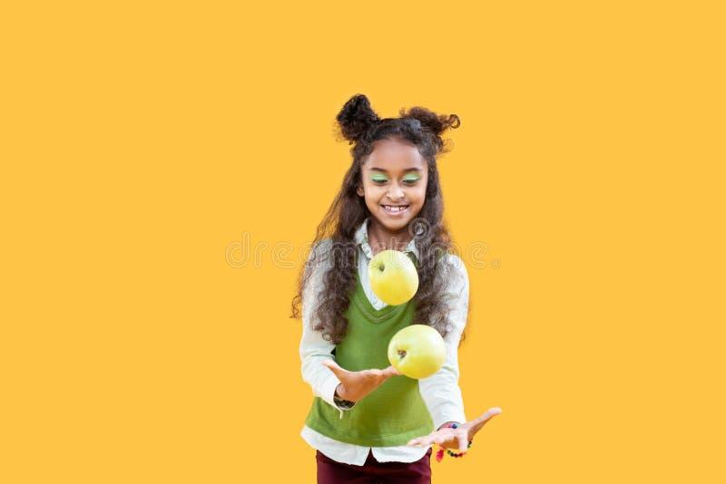 Radosny ładny dzieciak bawić się z zielonymi jabłkami zdjęcia royalty free
