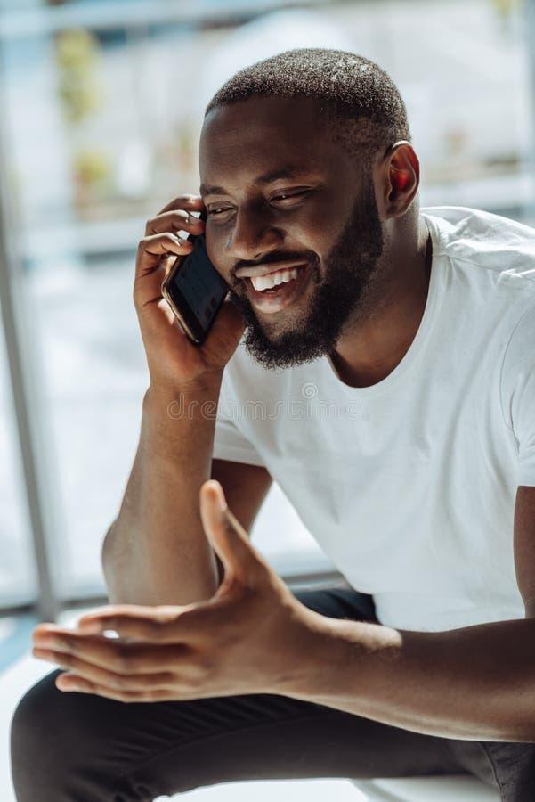 Radosny afro amerykański mężczyzna opowiada na mądrze telefonie fotografia stock