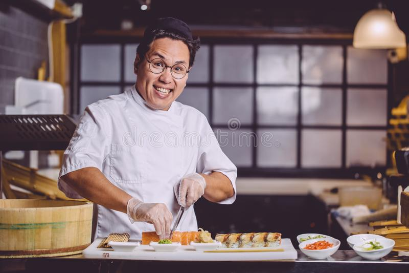 Radosny Azjatycki mężczyzna pracuje w suszi restauracji zdjęcie stock