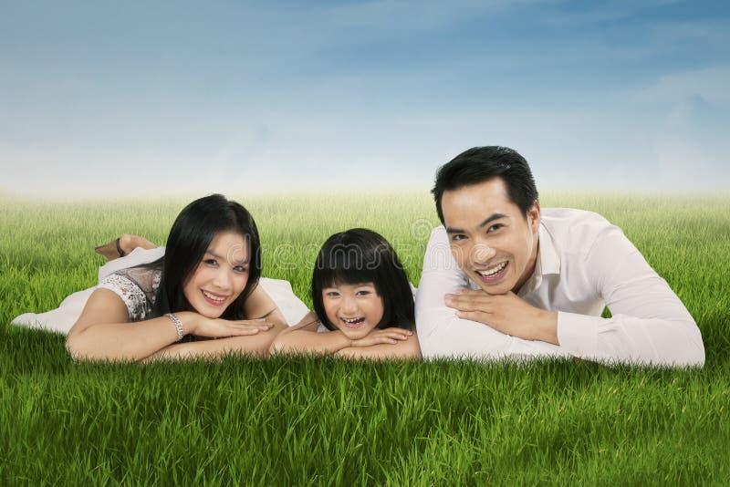 Radosny azjatykci rodzinny lying on the beach na trawie obrazy royalty free