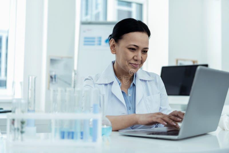 Radosny badacz pracuje na jej laptopie w lab obrazy stock