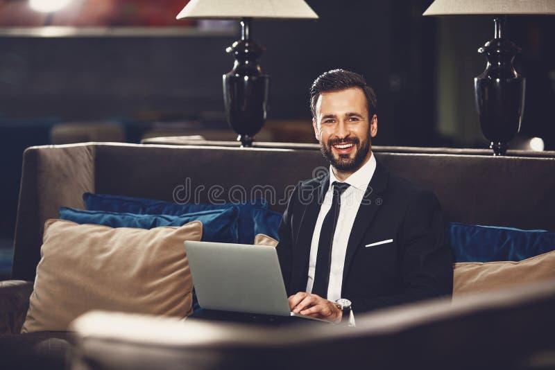Radosny biznesmen siedzÄ…cy w restauracji i trzymajÄ…cy laptop fotografia royalty free
