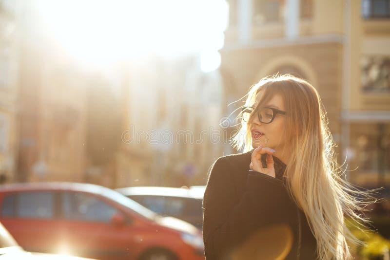 Radosny blondynka model jest ubranym szkła i odprowadzenie puszka pogodną ulicę Opróżnia przestrzeń fotografia stock