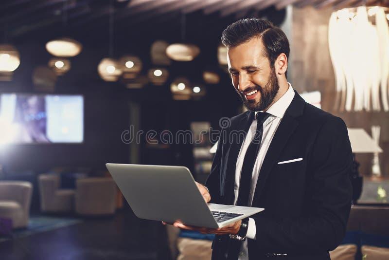 Radosny brodaty mężczyzna trzymajÄ…cy nowoczesny laptop i patrzÄ…cy na jego ekran zdjęcia royalty free