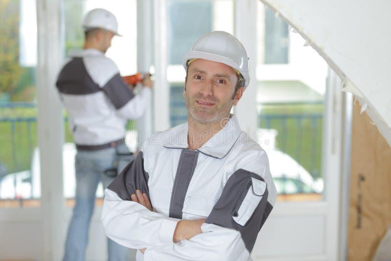 Radosny budowniczy ono uśmiecha się podczas gdy stojący indoors zdjęcia stock