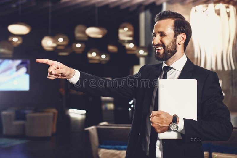 Radosny człowiek śmiejący się, stojąc przy swoim nowoczesnym urządzeniu obraz stock
