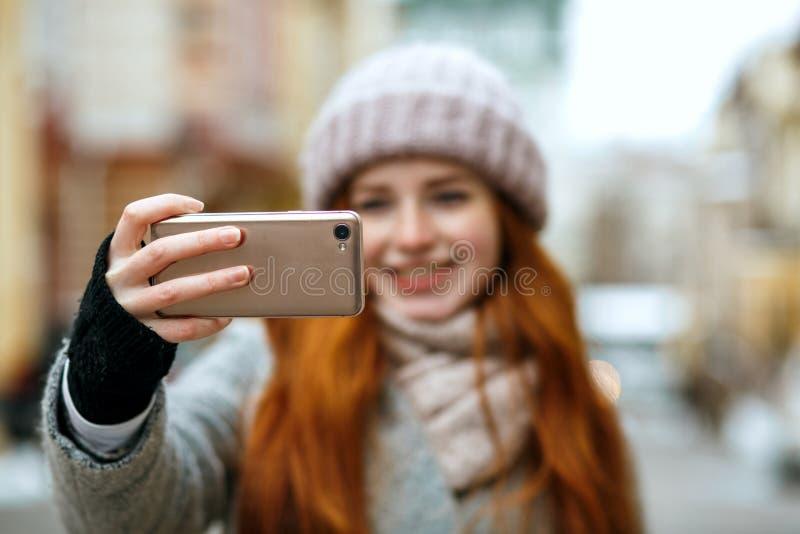 Radosny czerwieni głowy model w zimy odzieży bierze selfie na jej motłochu zdjęcie royalty free