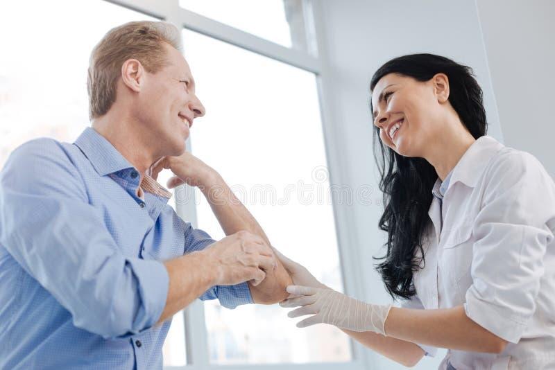 Radosny dermatolog cieszy się rozmowę z pacjentem w szpitalu fotografia royalty free