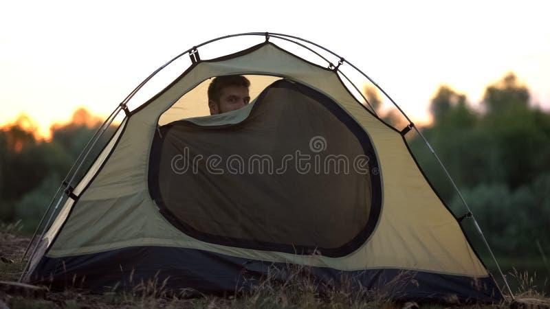 Radosny mężczyzna zapina kopuła namiot, przygotowywa spać w dzikim, wygodnym odpoczynku, fotografia royalty free