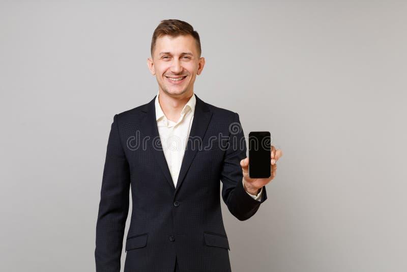 Radosny młody biznesowy mężczyzna w klasycznym czarnym kostiumu i koszula mienia telefonie komórkowym z puste miejsce pustym ekra obraz stock