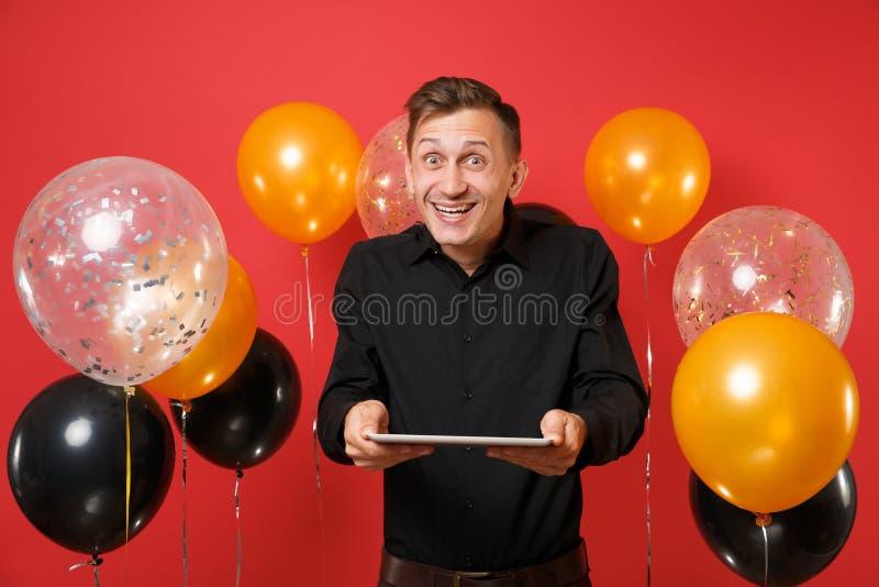 Radosny młody człowiek w czarnym klasycznym koszulowym mieniu i używać pastylka komputeru osobistego komputer na jaskrawego czerw obrazy stock