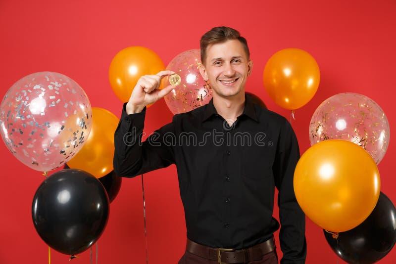 Radosny młody człowiek w klasycznej koszulowej chwyta bitcoin metalu monecie złotego koloru przyszłościowa waluta na czerwonego t obraz royalty free