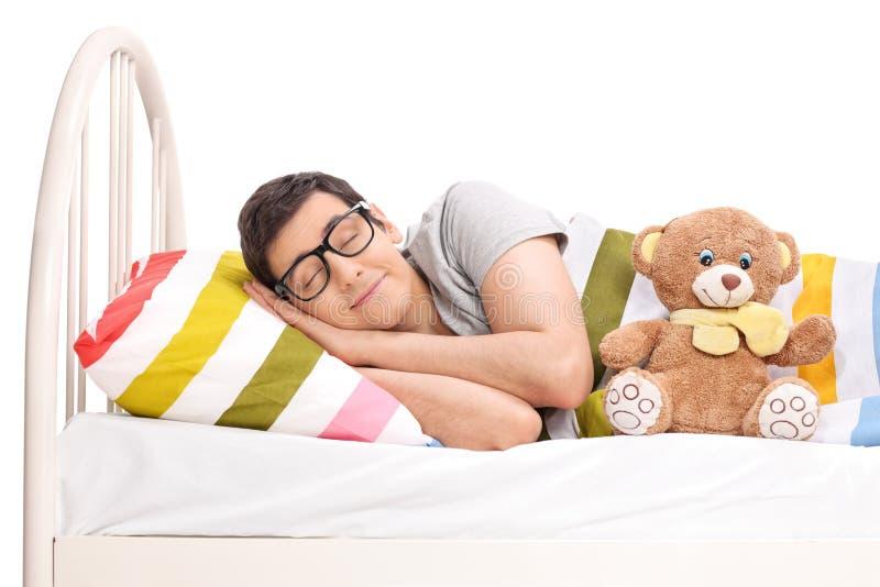 Radosny mężczyzna dosypianie w łóżku z misiem zdjęcie royalty free