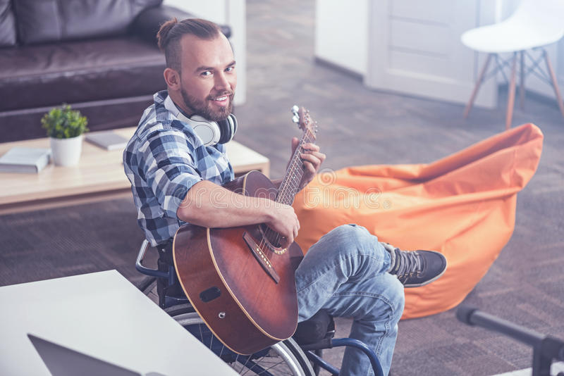 Radosny mężczyzna na wózku inwalidzkim bawić się gitarę w rozsądnym studiu nagrań obraz royalty free