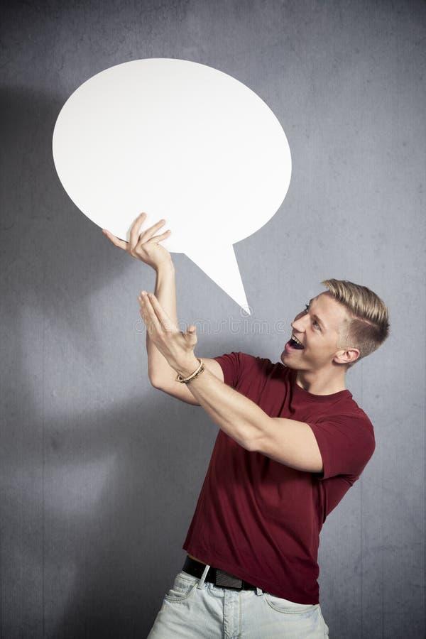 Radosny mężczyzna przedstawia biel mowy pustego balon. zdjęcia royalty free