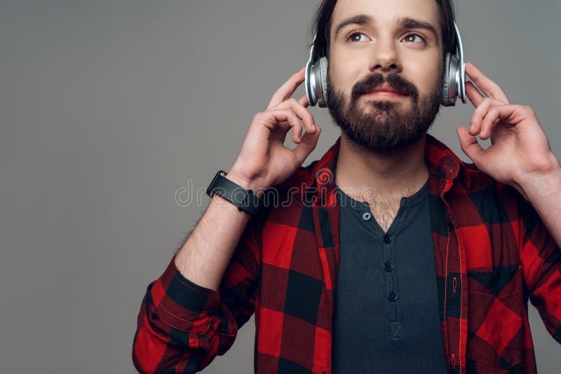 Radosny mężczyzna słucha muzyka z hełmofonami obrazy stock