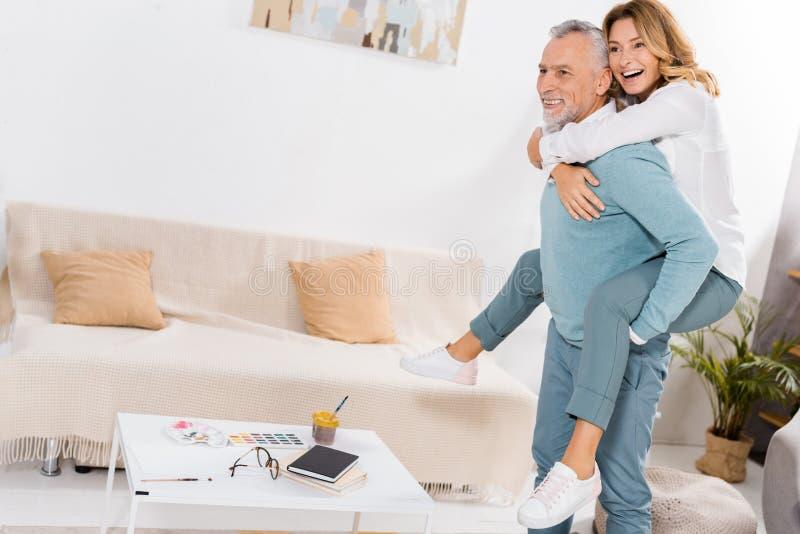 radosny mężczyzna w Å›rednim wieku, który jeździ na baranie do piÄ™knej żony w salonie zdjęcie royalty free