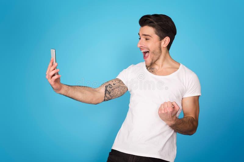 Radosny mężczyzna z telefon komórkowy odświętności zwycięstwem obrazy stock