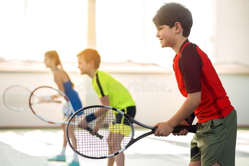 Radosny męski dzieciak bawić się tenisa z przyjaciółmi obrazy stock