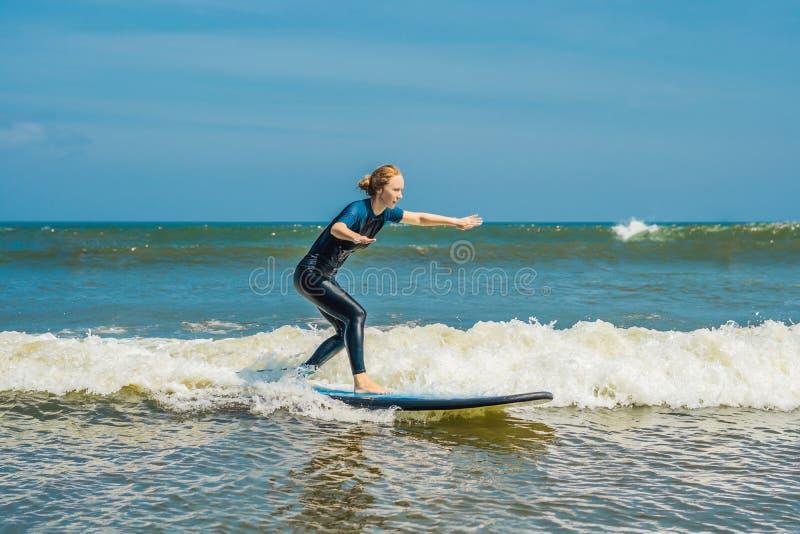 Radosny młodej kobiety beginner surfingowiec z błękitną kipielą zabawę na małych dennych falach Aktywny rodzinny styl życia, zalu obrazy royalty free