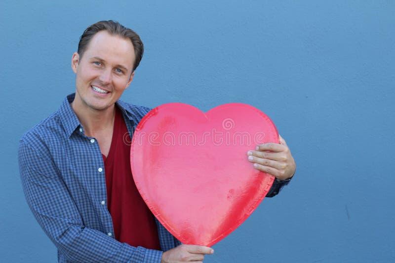 Radosny młody człowiek trzyma dużego czerwonego serce odizolowywający na błękitnym tle zdjęcia royalty free