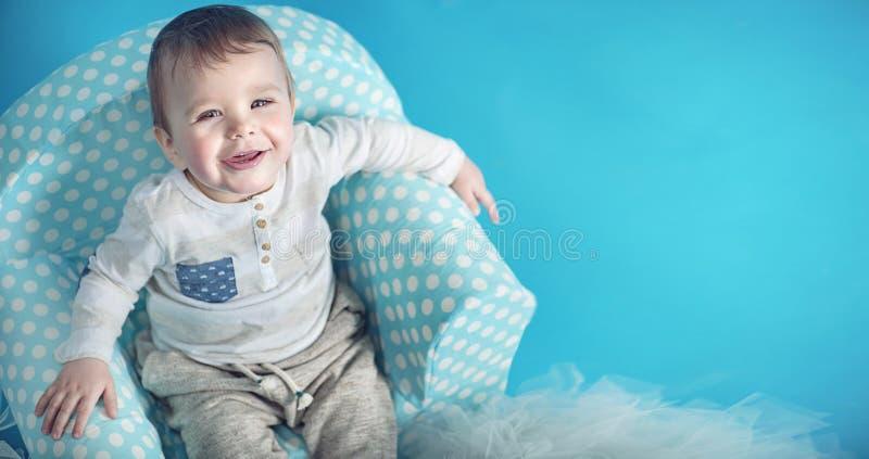 Radosny mały mężczyzna obsiadanie na wygodnym karle zdjęcia stock